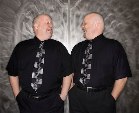 Caucasian bald mid adult identical twin men looking at each other laughing. Stock Photo - Budget Royalty-Free & Subscription, Code: 400-04451218