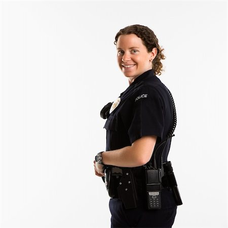 female police officer happy - Portrait of mid adult Caucasian policewoman standing with hand on gun holster looking over shoulder at viewer smiling. Stock Photo - Budget Royalty-Free & Subscription, Code: 400-04468892