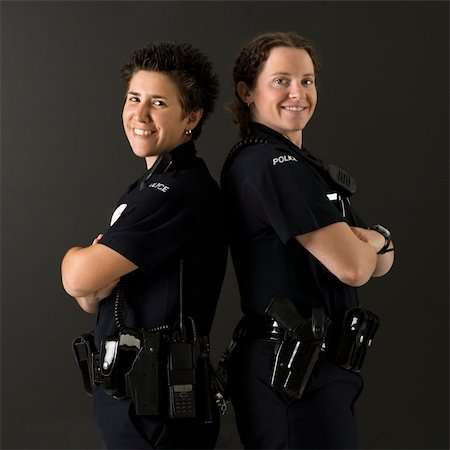 female police officer happy - Portrait of two mid adult Caucasian policewomen standing back to back looking over their shoulders smiling at viewer. Stock Photo - Budget Royalty-Free & Subscription, Code: 400-04468905