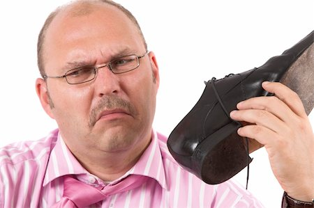 sweaty businessman - Businessman holding one of his shoes close to his nose pulling a face Stock Photo - Budget Royalty-Free & Subscription, Code: 400-04463678