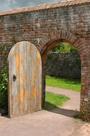 Old open arched wooden door set into an old red brick wall and leading to a grassed area beyond. Stock Photo - Budget Royalty-Free & Subscription, Code: 400-04476357