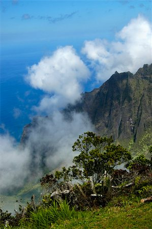 Majestic mountains, cloud cover and brilliant blue sky and ocean waters awes visitors to Na Pali Overlook. Stock Photo - Budget Royalty-Free & Subscription, Code: 400-04495115
