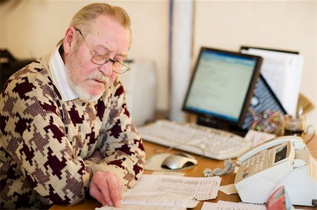 Senior at work place in office with computer notes and fax Stock Photo - Budget Royalty-Free & Subscription, Code: 400-04495700