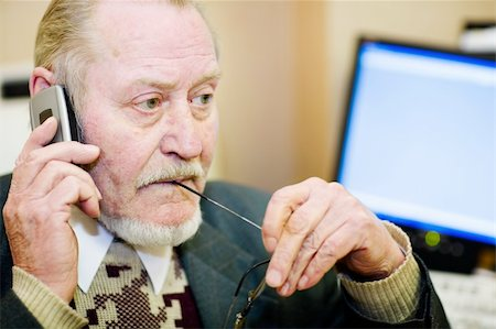 Mature businessman talking on the phone and  checking out a document on his computer monitor. Stock Photo - Budget Royalty-Free & Subscription, Code: 400-04495753