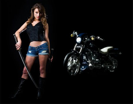 Attractive sexy woman in shorts holding a samurai sword standing beside a motorcycle on black Stock Photo - Budget Royalty-Free & Subscription, Code: 400-04502114