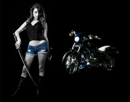 Attractive sexy woman in shorts holding a samurai sword standing beside a harley motorcycle on black Stock Photo - Budget Royalty-Free & Subscription, Code: 400-04502115