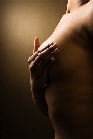 Young adult African-American female giving self breast exam. Stock Photo - Budget Royalty-Free & Subscription, Code: 400-04510098