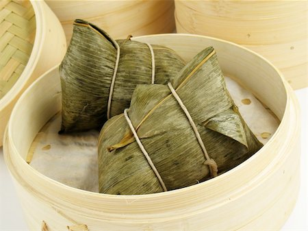 dumplings steamer - Steamed Chinese rice dumplings (zongzi) wrapped in bamboo leaves, filled with glutinous/sticky rice, pork, mushrooms, and peanuts. These are eaten during the Dragon Boat Festival. Stock Photo - Budget Royalty-Free & Subscription, Code: 400-04547879