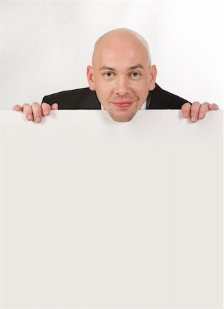 skinhead - Image of handsome male looking from behind white partition Stock Photo - Budget Royalty-Free & Subscription, Code: 400-04540206