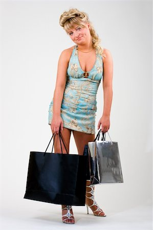 Tired smiling young woman with shopping bags Stock Photo - Budget Royalty-Free & Subscription, Code: 400-04567776