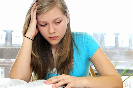 Teenage girl studying with textbooks looking unhappy Stock Photo - Budget Royalty-Free & Subscription, Code: 400-04560734