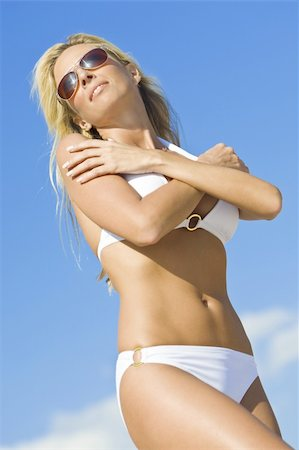 simsearch:400-04002563,k - A beautiful young blond woman wearing a white bikini and sunglasses shot against a blue sky Stock Photo - Budget Royalty-Free & Subscription, Code: 400-04561578