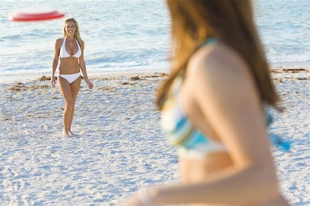 simsearch:400-04002563,k - A beautiful young blond woman wearing a white bikini playing frisbee at the beach with her friend Stock Photo - Budget Royalty-Free & Subscription, Code: 400-04562353