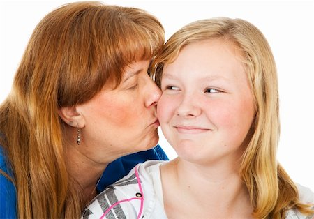 Mother kissing her pretty blond daughter who looks embarassed.  White background. Stock Photo - Budget Royalty-Free & Subscription, Code: 400-04585459