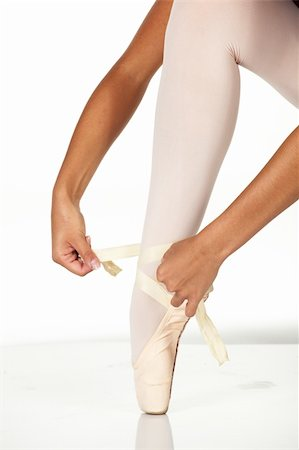 Young female ballet dancer showing how to tie a ballet Pointe Shoe against a white background. NOT ISOLATED Stock Photo - Budget Royalty-Free & Subscription, Code: 400-04609415