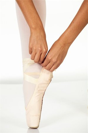 Young female ballet dancer showing how to tie a ballet Pointe Shoe against a white background. NOT ISOLATED Stock Photo - Budget Royalty-Free & Subscription, Code: 400-04609416
