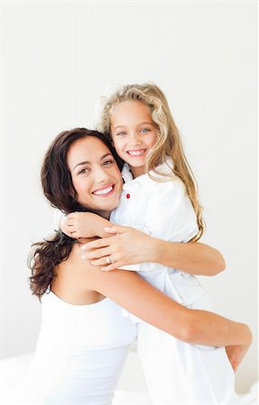 daughter kissing mother - Young Mother and daugther embracing on bed Stock Photo - Budget Royalty-Free & Subscription, Code: 400-04600015