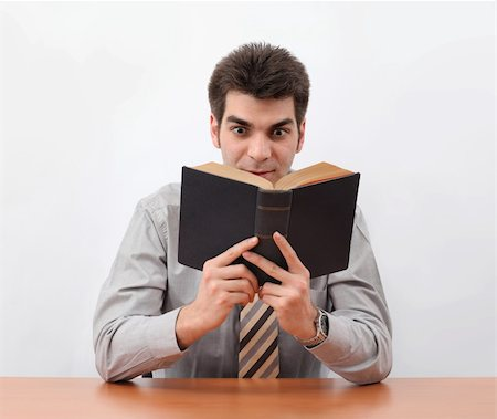 Young man holding and reading a old book with sitting at the table. Stock Photo - Budget Royalty-Free & Subscription, Code: 400-04601597