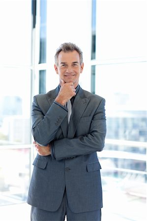 Smiling senior businessman standing in office Stock Photo - Budget Royalty-Free & Subscription, Code: 400-04614535