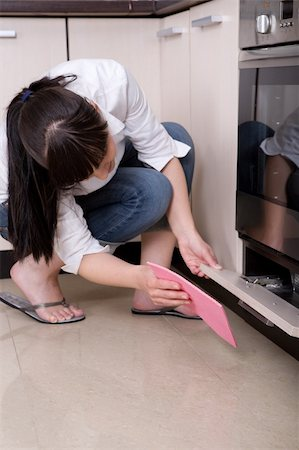young brunette woman cleaning kitchen Stock Photo - Budget Royalty-Free & Subscription, Code: 400-04616860