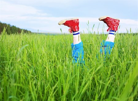 Amusing feet in the red gym shoes, cheerfully sticking out of a grass Stock Photo - Budget Royalty-Free & Subscription, Code: 400-04618807