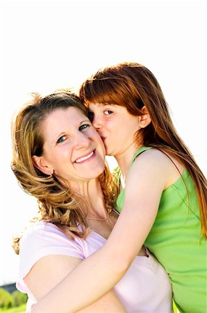 daughter kissing mother - Portrait of happy child hugging and kissing her mother Stock Photo - Budget Royalty-Free & Subscription, Code: 400-04613238