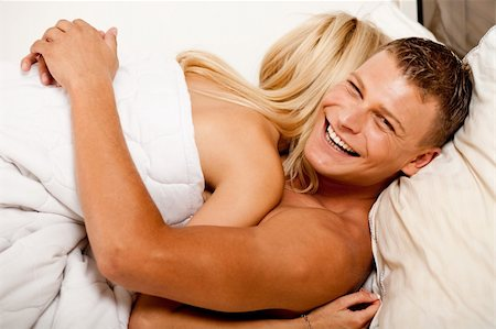 man smiling to camera while huggin his woman in bed Stock Photo - Budget Royalty-Free & Subscription, Code: 400-04627232