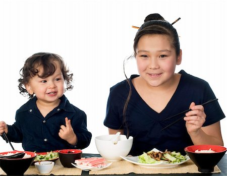 Two asian children have dinner,isolated on a white background. Stock Photo - Budget Royalty-Free & Subscription, Code: 400-04632962