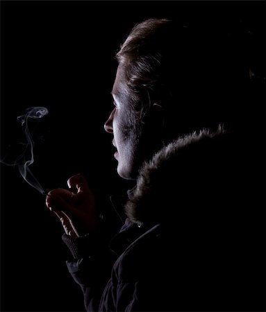 side face silhouette blowing - Strong contrast of woman blowing out a match with smoke clearly visible Stock Photo - Budget Royalty-Free & Subscription, Code: 400-04633068