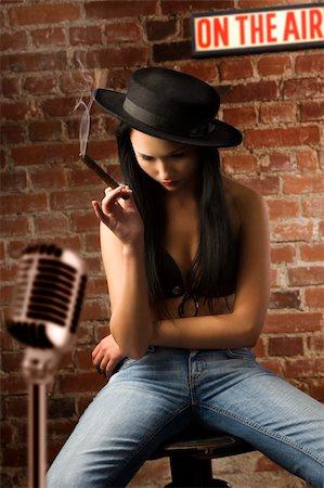 graceful asian woman sitting down and smoking a cigar near a bricks wall Stock Photo - Budget Royalty-Free & Subscription, Code: 400-04649688