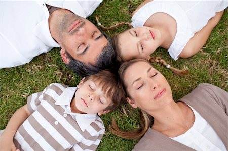 Parents and children sleeping in a park with heads together Stock Photo - Budget Royalty-Free & Subscription, Code: 400-04654755