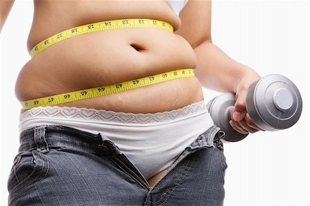 fat woman holding weight to exercise with measuring tape around her belly, a concept to fight obesity Stock Photo - Budget Royalty-Free & Subscription, Code: 400-04653659