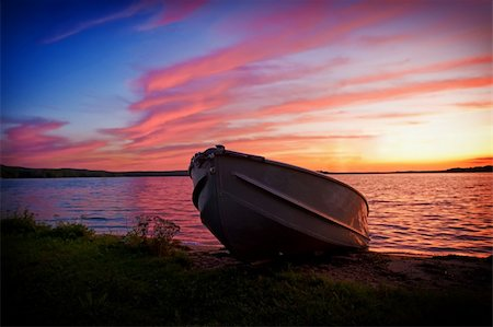 Fishing boat pulled up onto shore of a lake at sunset Stock Photo - Budget Royalty-Free & Subscription, Code: 400-04664276
