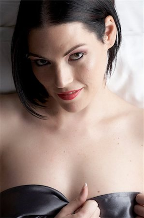 Sexy naked young caucasian adult woman with red lips, short black hair and a pierced eyebrow, covered in a dark satin sheet and sitting on a bed Stock Photo - Budget Royalty-Free & Subscription, Code: 400-04690599