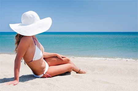 Young woman enjoying the sun sitting on a beach close to the sea Stock Photo - Budget Royalty-Free & Subscription, Code: 400-04702164