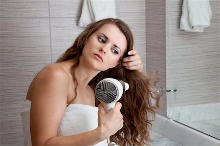 dressed in towel beautiful woman using fen at modern bathroom Stock Photo - Budget Royalty-Free & Subscription, Code: 400-04702613