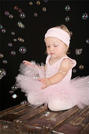 Cute blond toddler in ballet tutu reaching out to touch bubbles Stock Photo - Budget Royalty-Free & Subscription, Code: 400-04718879