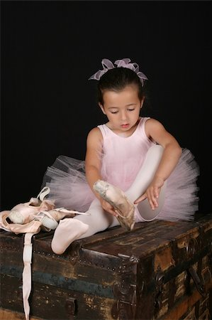 Cute little brunette girl trying on ballet pointe shoes Stock Photo - Budget Royalty-Free & Subscription, Code: 400-04712806