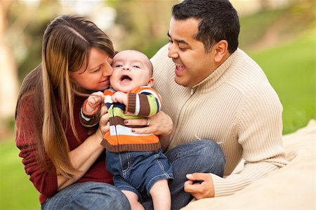 daughter kissing mother - Happy Mixed Race Parents Playing with Their Giggling Son. Stock Photo - Budget Royalty-Free & Subscription, Code: 400-04743690