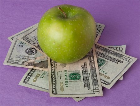 education loan - A green apple sits on top of a pile of $20 bills to illustrate the cost of education, food, or health care. Stock Photo - Budget Royalty-Free & Subscription, Code: 400-04758614