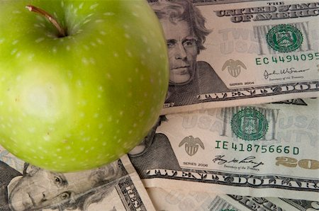 education loan - A green apple sits on top of a pile of $20 bills to illustrate the cost of education, food, or health care. Stock Photo - Budget Royalty-Free & Subscription, Code: 400-04758615