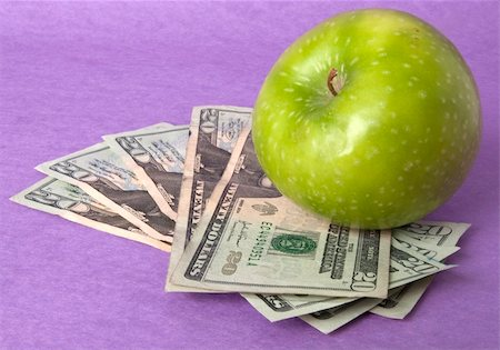 education loan - A green apple sits on top of a pile of $20 bills to illustrate the cost of education, food, or health care. Stock Photo - Budget Royalty-Free & Subscription, Code: 400-04758610