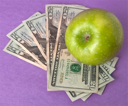 education loan - A green apple sits on top of a pile of $20 bills to illustrate the cost of education, food, or health care. Stock Photo - Budget Royalty-Free & Subscription, Code: 400-04758612