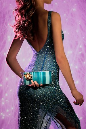 a nice dress woman hiding a christmas gift on her back Stock Photo - Budget Royalty-Free & Subscription, Code: 400-04759494