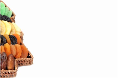 Christmas border made of Christmas tree shaped basket with variety of dried fruits. Isolated on white background, shallow dof Stock Photo - Budget Royalty-Free & Subscription, Code: 400-04753560