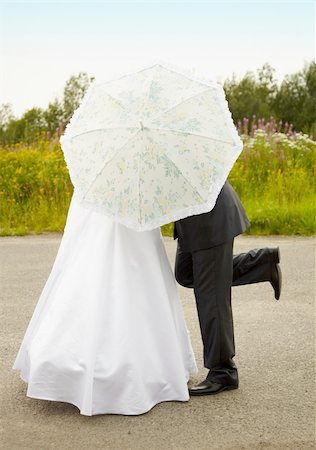 Young couple kissing hiding behind an umbrella Stock Photo - Budget Royalty-Free & Subscription, Code: 400-04766915