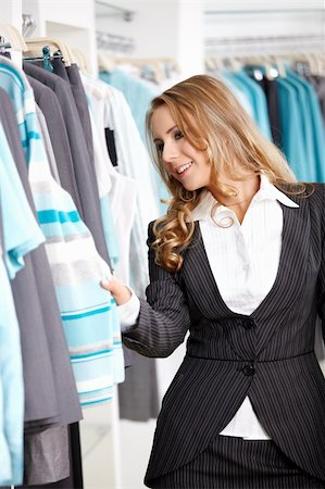 The young attractive girl considers clothes in shop Stock Photo - Budget Royalty-Free & Subscription, Code: 400-04778965