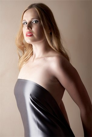Sexy young caucasian adult woman with red lips and blonde hair standing against a neutral brown wall, covered with a dark silk sheet. Single light source Stock Photo - Budget Royalty-Free & Subscription, Code: 400-04770232