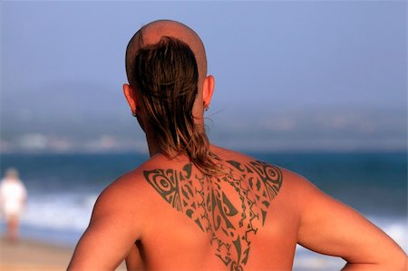 The young man with a beautiful tattoo on a coast of ocean Stock Photo - Budget Royalty-Free & Subscription, Code: 400-04788092
