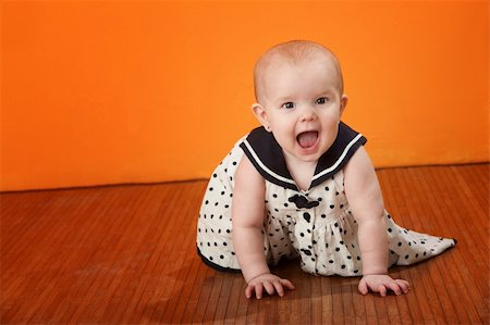 photo of class with misbehaving kids - A cute baby with polka dot dress crawls on a wooden floor Stock Photo - Budget Royalty-Free & Subscription, Code: 400-04783208
